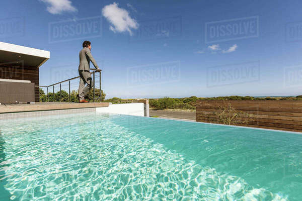 Businessman standing on luxury sunny patio with infinity pool, looking at view Royalty-free stock photo