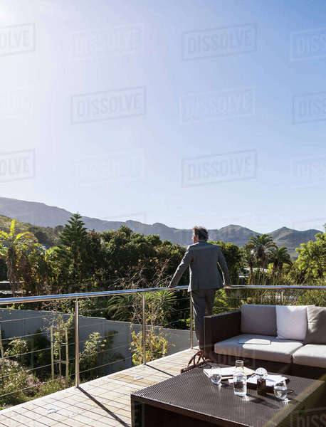 Pensive businessman on sunny balcony patio, looking at mountain view Royalty-free stock photo