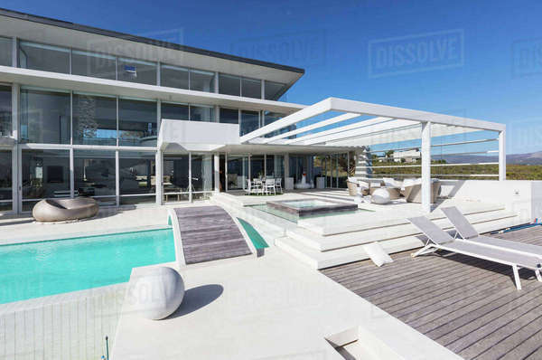 Sunny modern luxury home showcase exterior with lounge chairs and swimming pool Royalty-free stock photo