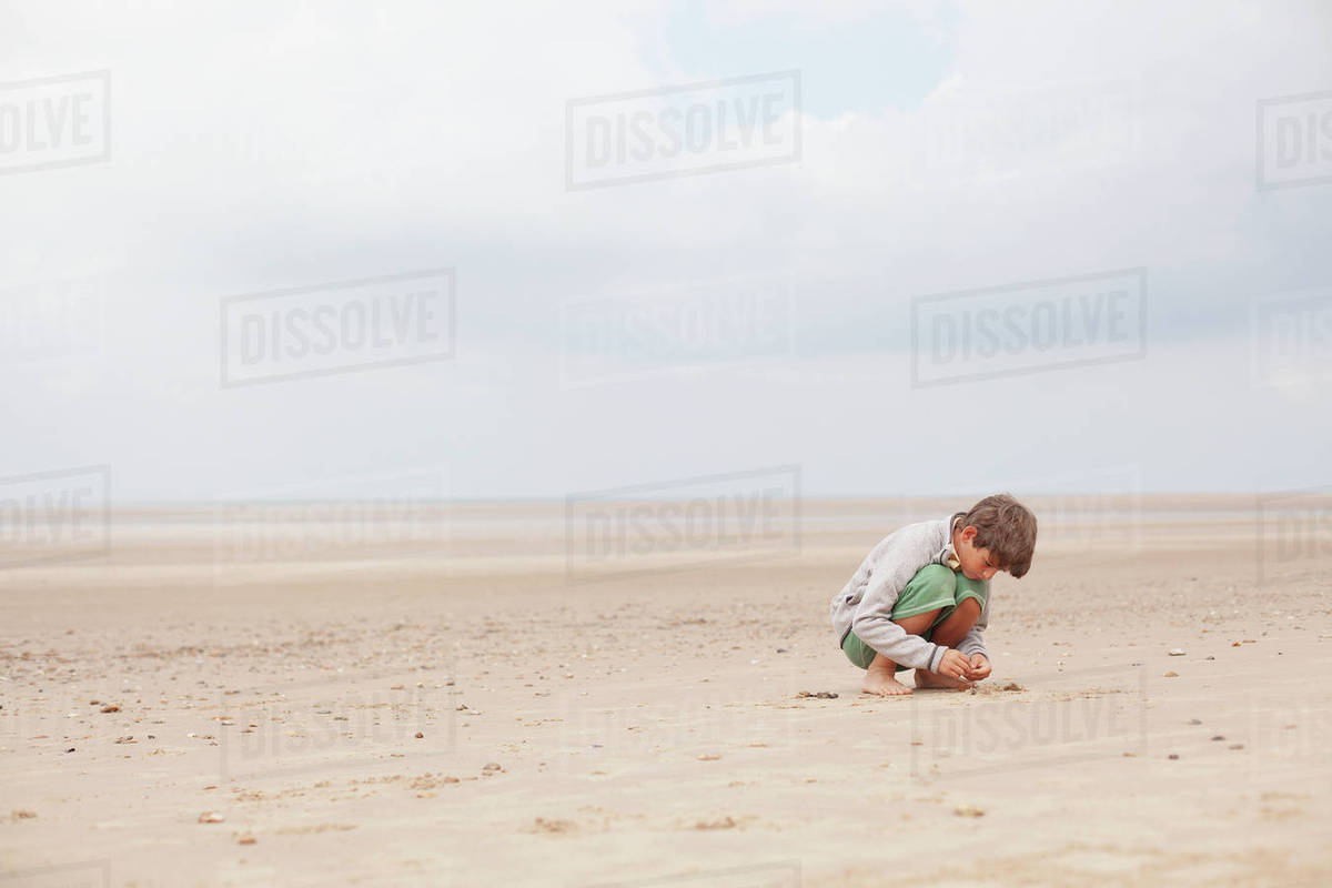 Boy playing in sand on overcast summer beach Royalty-free stock photo
