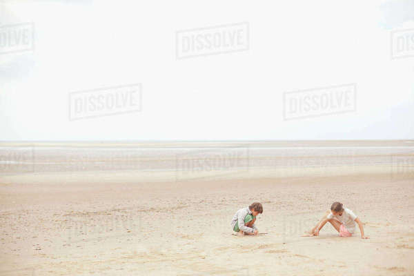 Brother and sister playing in sand on overcast summer beach Royalty-free stock photo