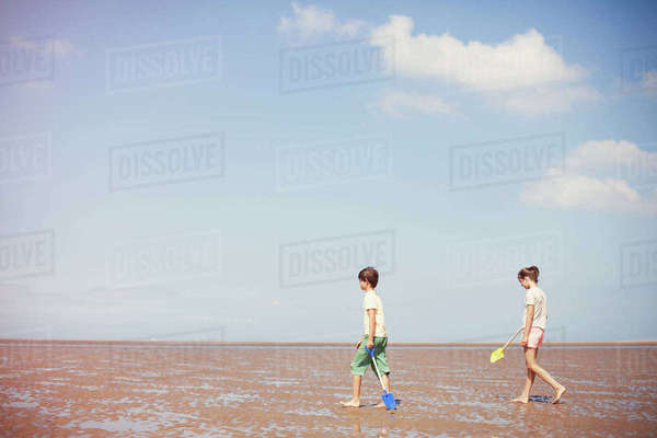 Brother and sister with shovels in wet sand on sunny summer beach below blue sky Royalty-free stock photo