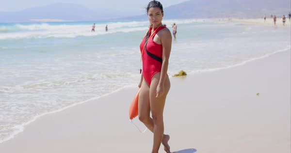 b5ef06b9b6f4 Woman in bright red lifeguard outfit whistle floatation device and calm  expression on beach with swimmers