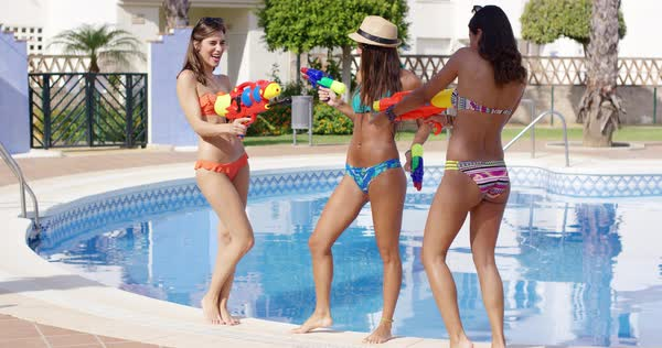 Three Sexy Young Women Playing With Water Guns At The Side Of A Tropical Swimming Pool