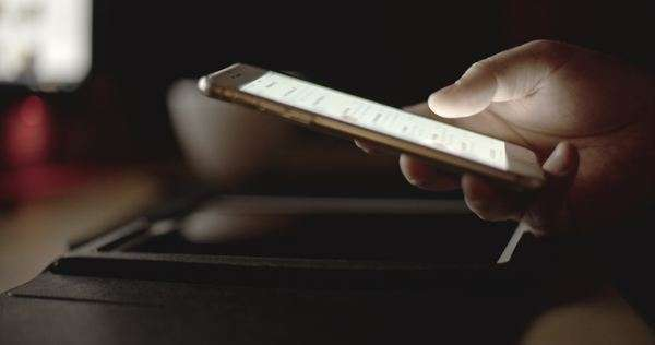 Close-up of a man's thumb browsing the touchscreen of a mobile phone in the dark Royalty-free stock video