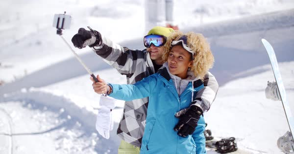 b88903d6ab Fun young couple wearing ski clothes and goggles posing in the snow for a  selfie on