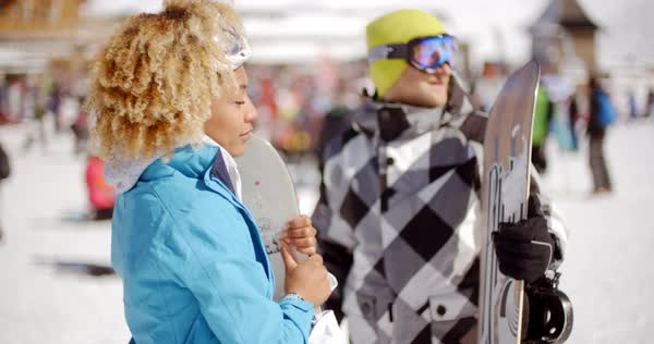 122120791e Cute woman in curly hair and blue coat holding snowboard on ski slope  crowded with skiers