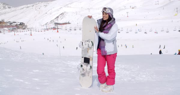 cd45ede7d0 Young woman standing in the snow waiting with her snowboard at a mountain  ski resort looking