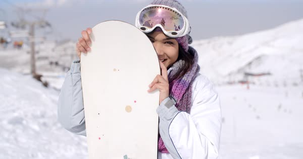 5f9372388e Laughing young woman wearing fashionable ski clothes and goggles posing  with her snowboard on a snowy