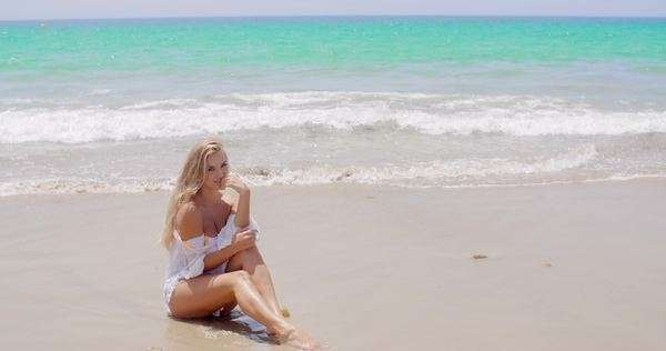 Pretty blond woman in sexy white summer wear sitting at the beach and smiling at the camera against beautiful ocean background. Royalty-free stock video