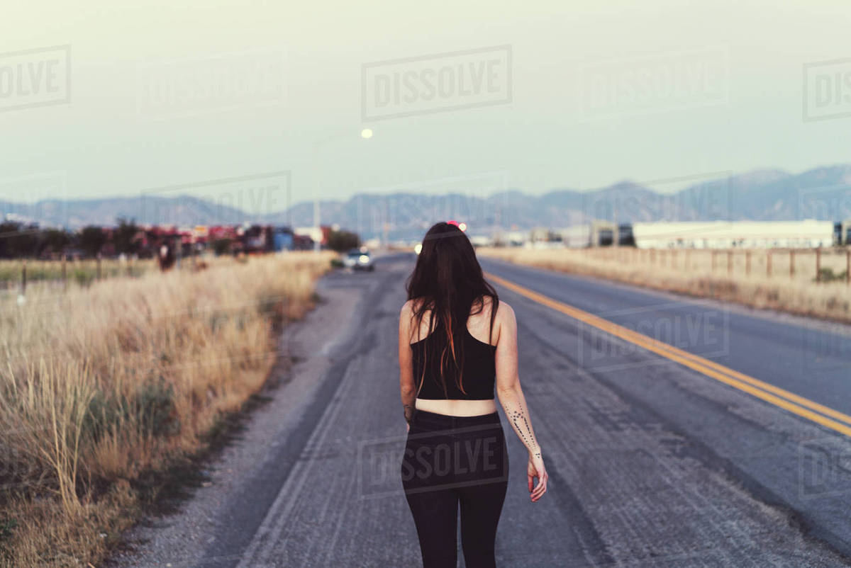 Woman walking down street with mountains in the background Royalty-free stock photo
