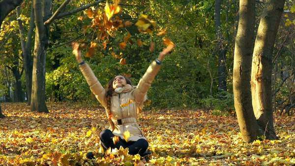 Young girl having fun throwing yellow leaves in the sunny fall park, front view, slow motion Royalty-free stock video