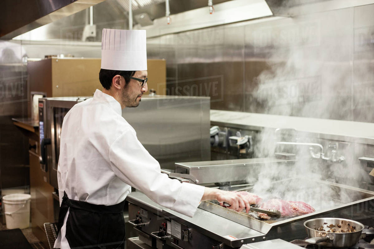 An Asian chef working with fresh meat on the grill D1024_104_201