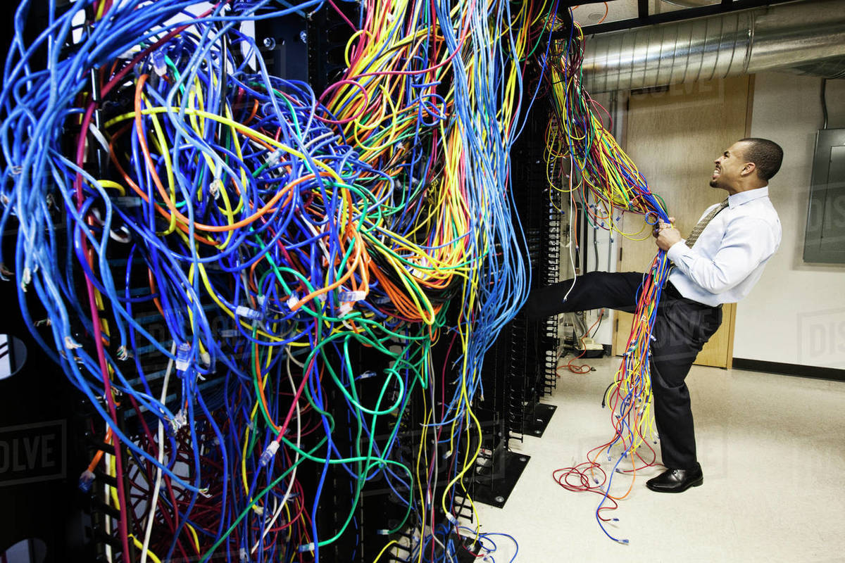 a black male technician pulling on a tangled mess of cat 5 cables in a computer server room. Black Bedroom Furniture Sets. Home Design Ideas
