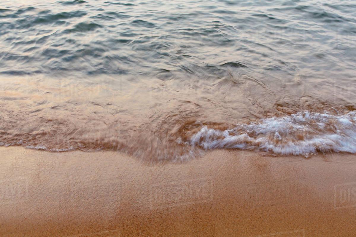 Detail of waves crashing on beach at dusk, long exposure stock photo