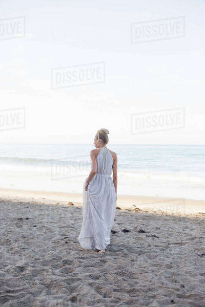 Blond woman wearing a long dress standing on a sandy beach. Royalty-free stock photo