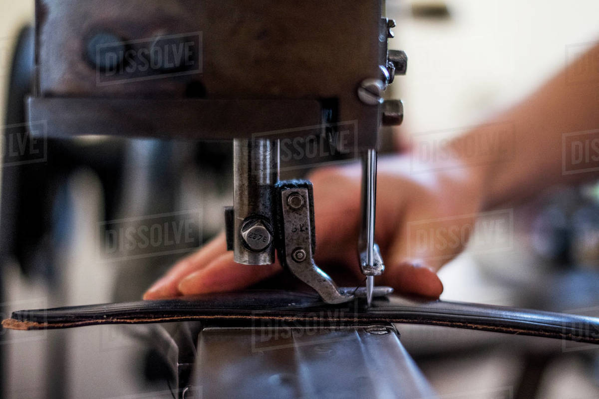 Close up of person sewing piece of leather to make a saddle. Royalty-free stock photo