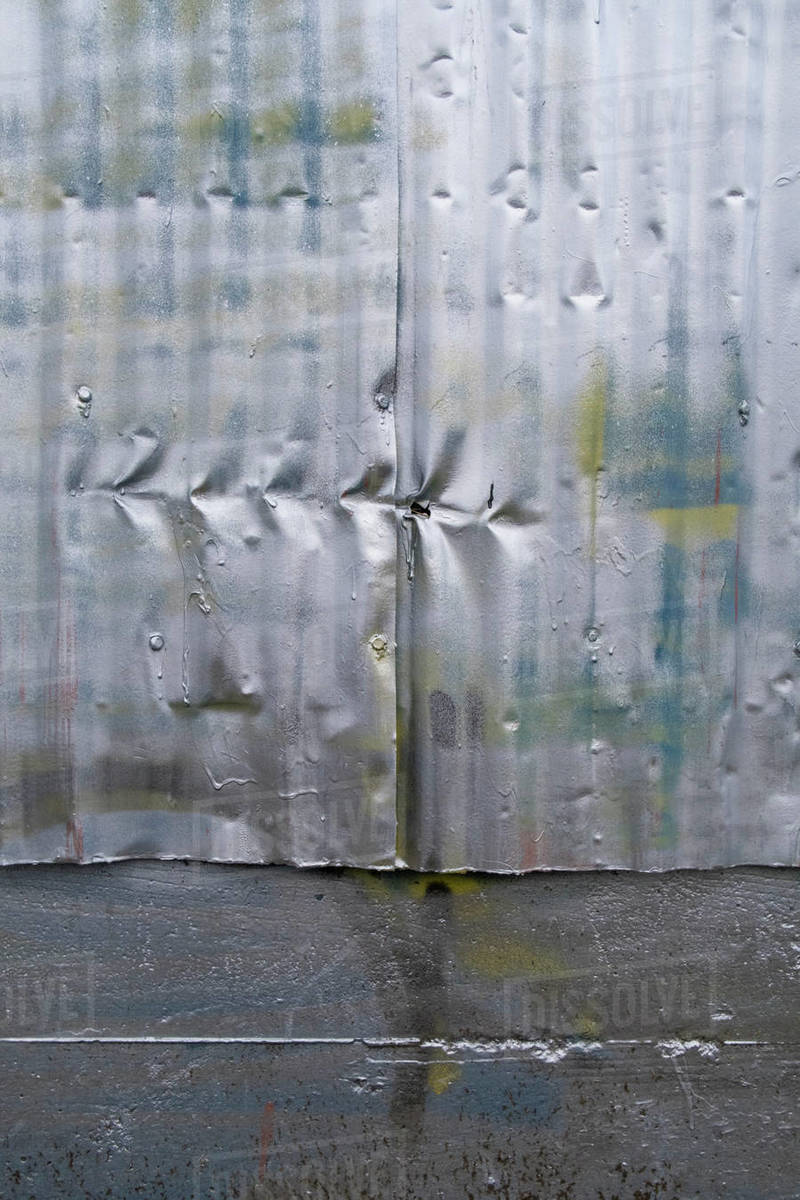 Row of indentation marks on silver spray painted metal wall, close up Royalty-free stock photo