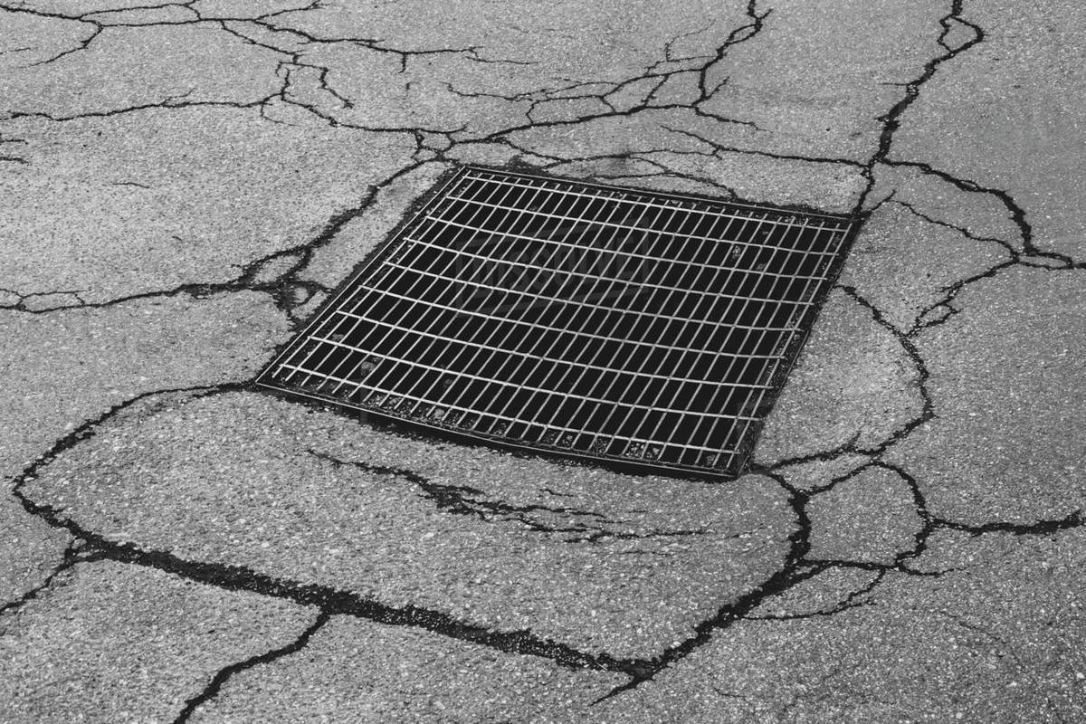 Drainage sewer grate on worn and cracked asphalt street Royalty-free stock photo