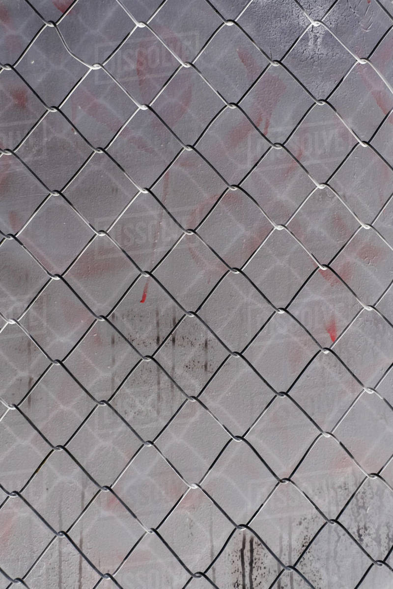 Inverted image of chainlink fence against graffiti covered grey wall, close up Royalty-free stock photo