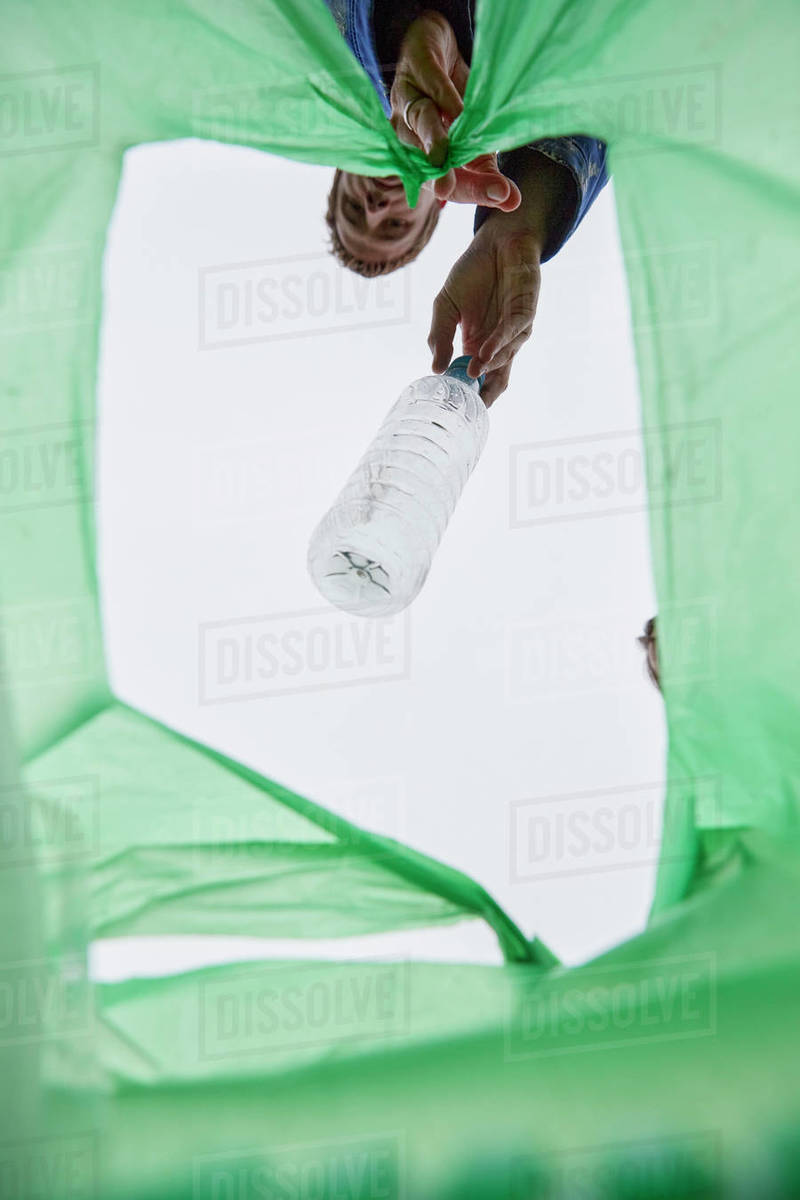 Man dropping a plastic bottle into a green plastic bag, view from inside bag. Royalty-free stock photo