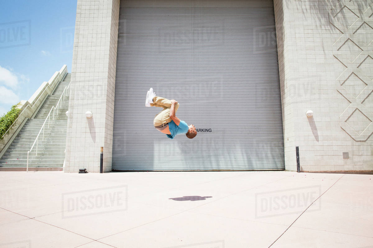 Young man somersaulting in front of a garage door.  Royalty-free stock photo