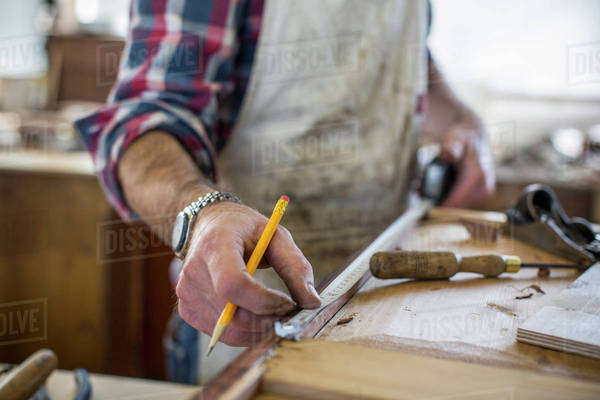 An antique furniture restorer measuring a piece of wood.  Royalty-free stock photo