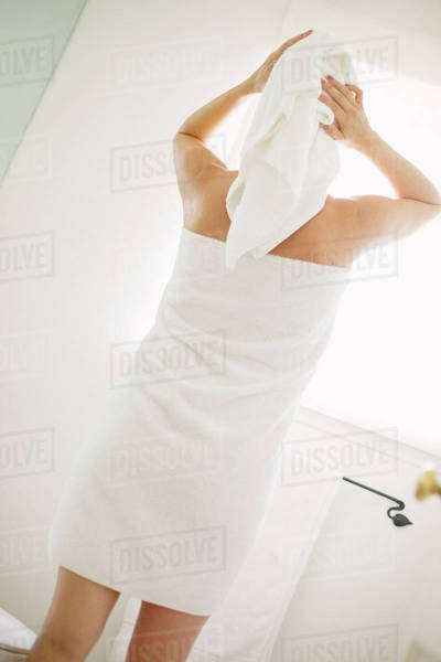 Woman wrapped in a white towel standing in a bathroom, wrapping her hair in a towel. Royalty-free stock photo