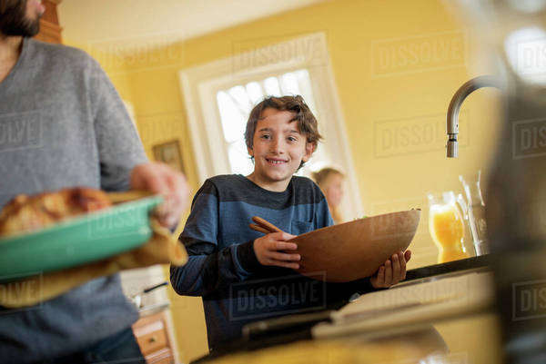 A woman carrying prepared food to the table. A boy with a large wooden bowl. Royalty-free stock photo