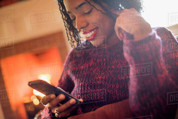 A woman checking her cell phone and smiling. Royalty-free stock photo