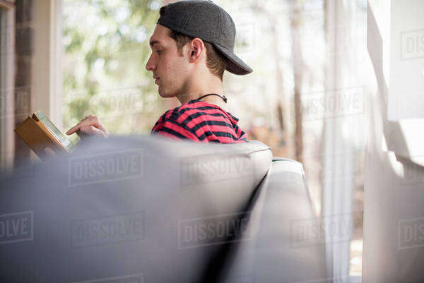 Man wearing a baseball cap backwards, sitting on a sofa, looking at a digital tablet. Royalty-free stock photo