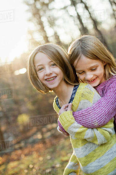 Two smiling girls in a forest, hugging each other. Royalty-free stock photo