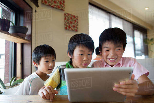 Three boys sitting at a table, looking at a digital tablet, smiling. Royalty-free stock photo