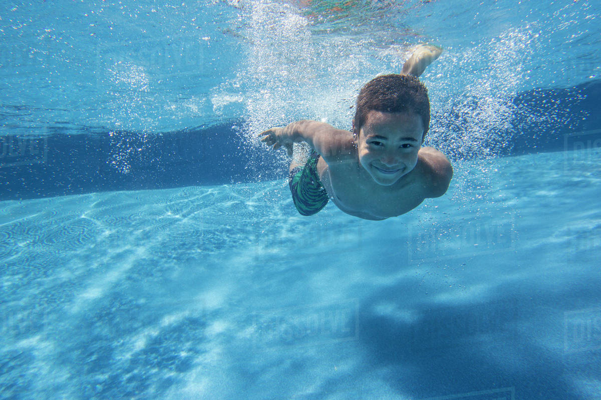 A boy swimming underwater smiling at the camera.  Royalty-free stock photo