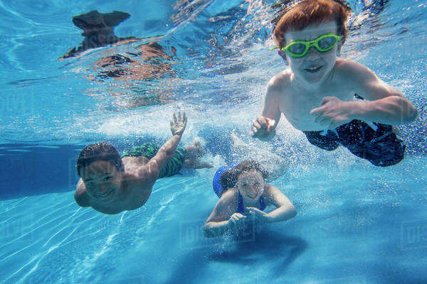 Three children swimming underwater, smiling at the camera.  Royalty-free stock photo