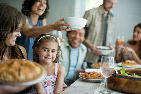 A family gathering for a meal. Adults and children around a table.  Royalty-free stock photo