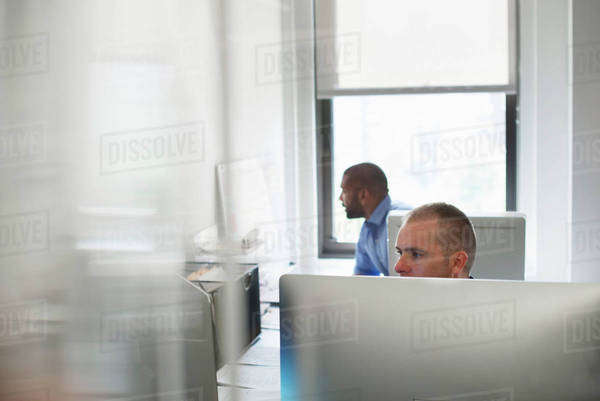 Two men working in an office, using computers. One looking at a wall chart.  Royalty-free stock photo
