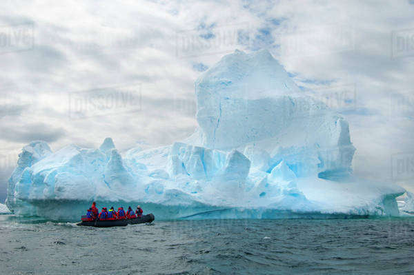 People in small inflatible zodiac rib boats passing icebergs and ice floes on the calm water around small islands of the Antarctic. Royalty-free stock photo