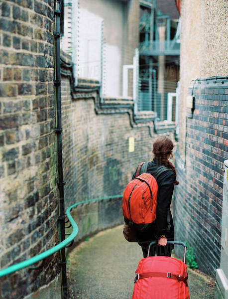A woman walling down a narrow street, pulling a suitcase and holdin an orange backpack.  Royalty-free stock photo