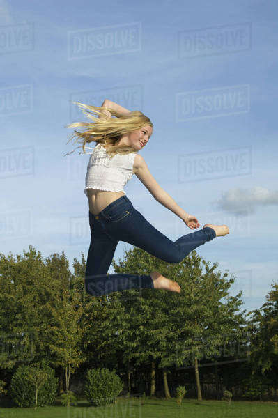 Teenage girl with long blond hair jumping in the air. Royalty-free stock photo
