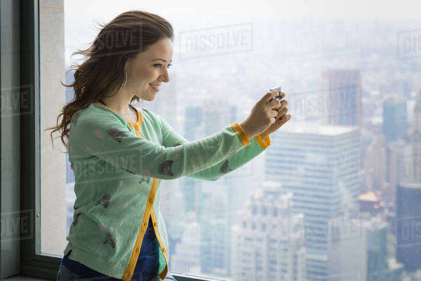 Urban Lifestyle. A young woman using her camera to take a picture from an observation deck over the city rooftops.  Royalty-free stock photo