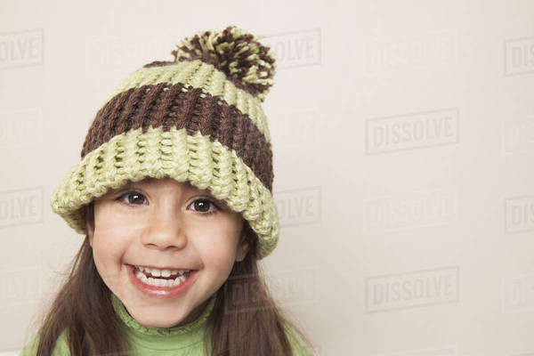 A young child with long brown hair, wearing a knitted hat with a pompom. Royalty-free stock photo