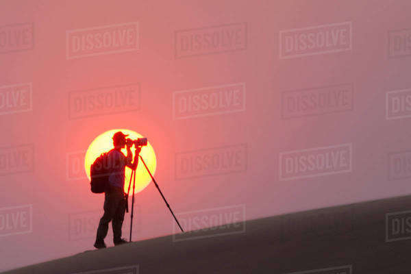 Photographer silhouetted in the setting sun in the Namib Desert, Namibia Royalty-free stock photo