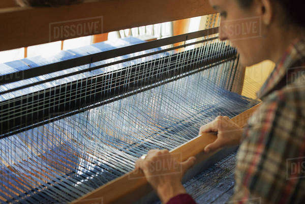 A woman seated at a wooden handloom creating a handwoven woollen fabric, with a blue and white pattern.  Royalty-free stock photo