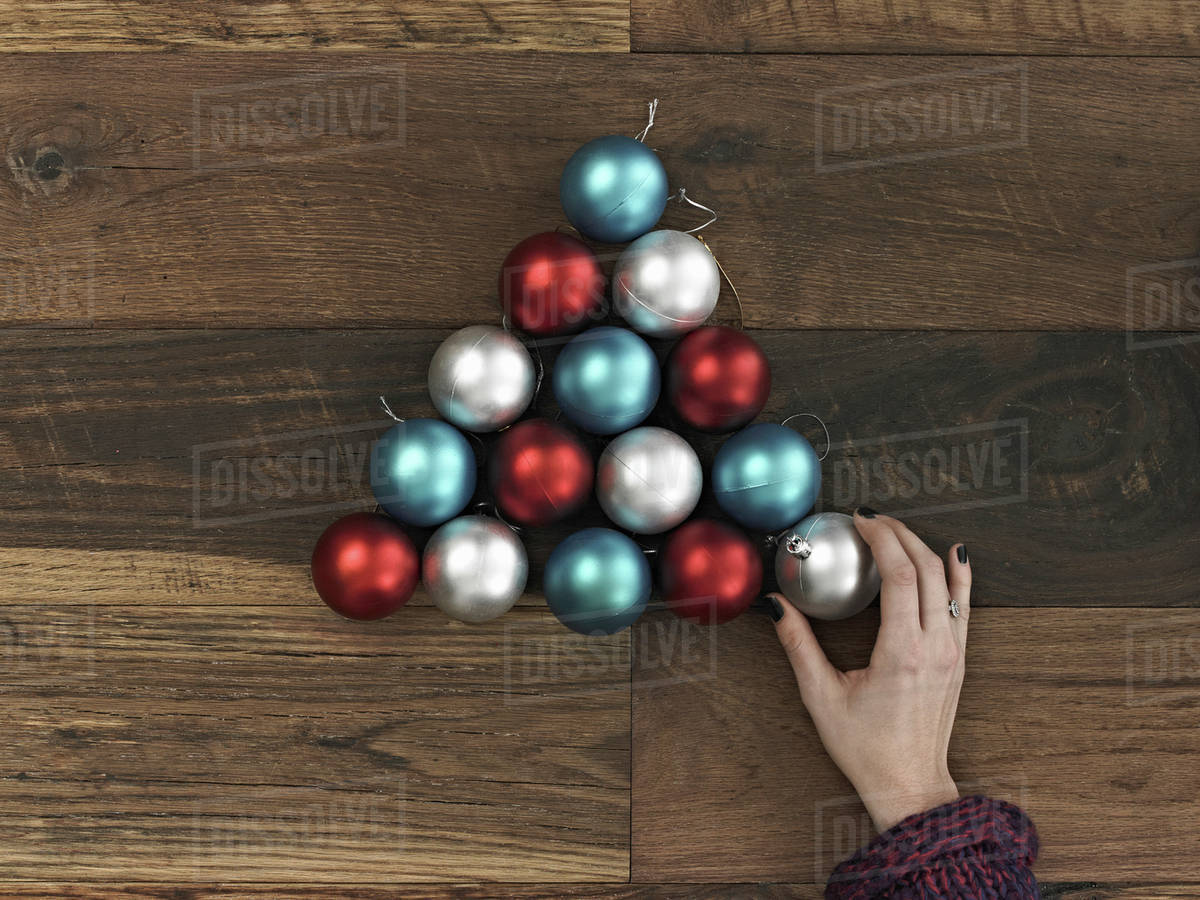 A Collection Of Blue Red And Silver Ornaments Arranged In Triangular Shape On Wooden Board Christmas Tree Person S Hand Placing The Final