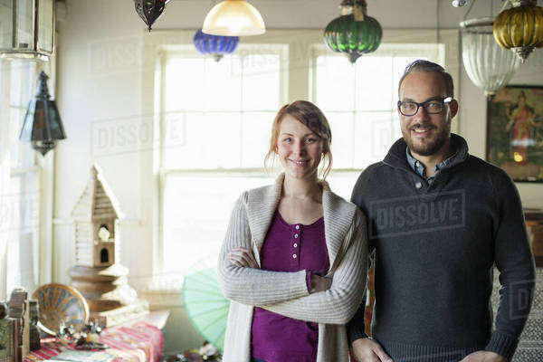 Two people standing in a store full of antique objects, a couple running a business.  Royalty-free stock photo