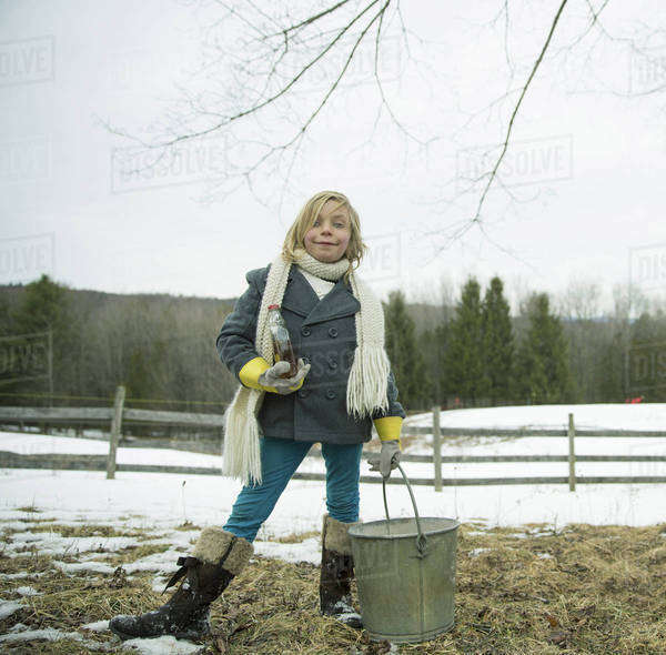 A girl in the snow, carrying a metal bucket.  Royalty-free stock photo