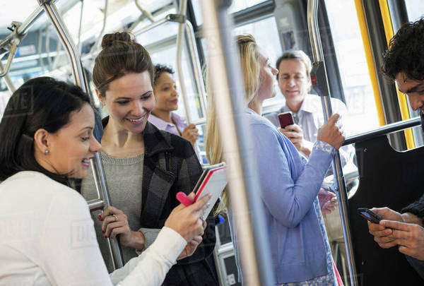New York City park. People, men and women on a city bus. Public transport. Two women looking at a handheld digital tablet.  Royalty-free stock photo