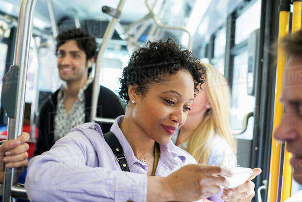 New York City park. People, men and women on a city bus. Public transport. Keeping in touch. A young woman checking or using her cell phone. Royalty-free stock photo