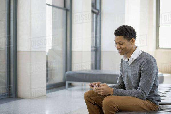 Urban Lifestyle. A young man sitting in a lobby, on a bench seat. Using his mobile phone.  Royalty-free stock photo